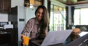Ordenador portátil del uso de la muchacha en la cocina que charla el interior moderno de la casa del estudio en línea de la mujer metrajes