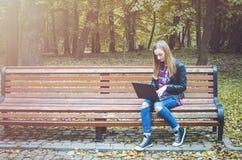 Ordenador portátil del uso de la muchacha del inconformista en un parque Imágenes de archivo libres de regalías
