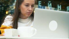 Ordenador portátil del uso de la mujer en café al aire libre almacen de video