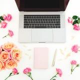 Ordenador portátil, diario, flores de las rosas, melcocha y accesorios en el fondo blanco Endecha plana Visión superior Concepto  Fotos de archivo