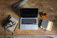 Ordenador portátil, diarios, cámara de la foto del vintage y taza de café en el tablero de la mesa de madera Fotos de archivo