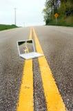 Ordenador portátil en el camino Foto de archivo libre de regalías