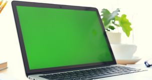 Ordenador portátil en el escritorio con la pantalla verde metrajes
