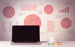 Ordenador portátil en el escritorio de oficina con los gráficos circulares de las ventas Fotos de archivo libres de regalías
