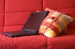 Ordenador portátil en el sofá rojo foto de archivo libre de regalías