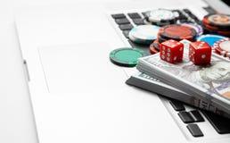Ordenador portátil en línea del casino Teclado y microprocesadores del ordenador portátil con los dólares del efectivo de los dad foto de archivo