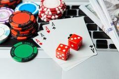 Ordenador portátil en línea del casino Teclado del ordenador portátil y microprocesadores con los dados y naipes y dólares del ef foto de archivo