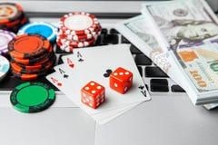 Ordenador portátil en línea del casino Teclado del ordenador portátil y microprocesadores con los dados y naipes y dólares del ef foto de archivo libre de regalías