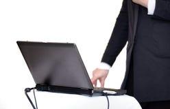 Ordenador portátil en la tabla con la mano Fotos de archivo