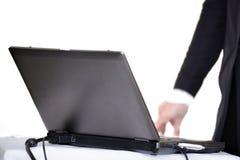 Ordenador portátil en la tabla con la mano Foto de archivo libre de regalías