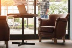 Ordenador portátil en la tabla de madera en cafetería con el hombre que usa phon móvil Foto de archivo libre de regalías