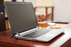 Ordenador portátil en la tabla de madera en hogar Foto de archivo libre de regalías