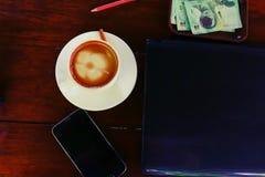 Ordenador portátil en la taza de café de la tienda del café y el teléfono móvil en la tabla Foto de archivo libre de regalías