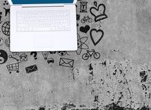 Ordenador portátil en piso concreto con los diversos iconos sociales Fotos de archivo libres de regalías