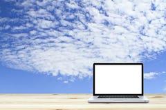 Ordenador portátil en piso de madera con el fondo del cielo imagenes de archivo