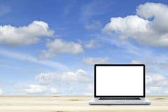 Ordenador portátil en piso de madera con el fondo del cielo blanco fotos de archivo