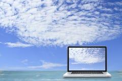 Ordenador portátil en piso de madera con el fondo del cielo Pantalla blanca imágenes de archivo libres de regalías