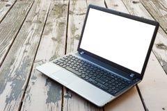Ordenador portátil en piso de madera con la pantalla en blanco fotografía de archivo