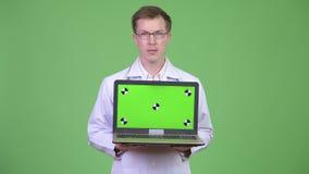 Ordenador portátil feliz de la pantalla del verde del doctor Showing Chroma Key del hombre metrajes