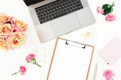 Ordenador portátil, flores de las rosas y tablero de plata en el fondo blanco Endecha plana Visión superior Concepto del blog del fotografía de archivo libre de regalías