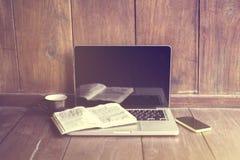 Ordenador portátil, libro y teléfono celular en un piso de madera Foto de archivo