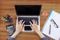 Ordenador portátil masculino del uso de las manos en el escritorio de madera fotografía de archivo