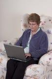 Ordenador portátil mayor maduro de la mujer, mirada seria Fotografía de archivo