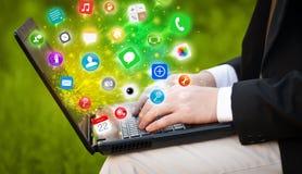 Ordenador portátil moderno del presionado a mano con los iconos móviles y los símbolos del app Imagenes de archivo
