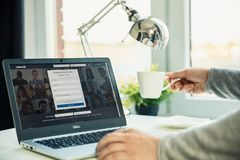 Ordenador portátil moderno en el escritorio en oficina con la página web de Linkedin en la pantalla fotografía de archivo