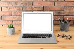 Ordenador portátil moderno en la tabla contra la pared de ladrillo Mofa para arriba imagen de archivo libre de regalías