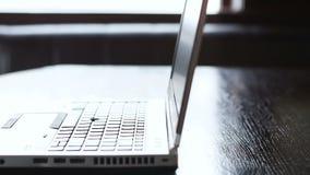 Ordenador portátil moderno en la tabla en la oficina, dispositivo para trabajar el proceso, acceso remoto metrajes