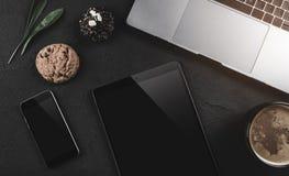 Ordenador portátil moderno, teléfono móvil, tableta, taza de café y galleta en fondo de piedra negro Visión superior con el espac fotografía de archivo