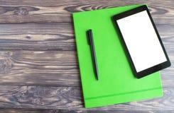 ordenador portátil negro y mentira negra de la pluma de bola en un semanario verde imágenes de archivo libres de regalías