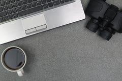 Ordenador portátil o cuaderno, binocular y taza de café en trabajo Imagenes de archivo