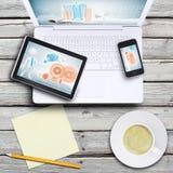 Ordenador portátil, PC de la tableta, smartphone y taza de café Imágenes de archivo libres de regalías