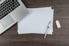 Ordenador portátil, pluma de papel y borrador en el escritorio del trabajo Foto de archivo