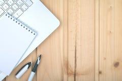 Ordenador portátil, pluma, libreta en superficie ligera de madera fotos de archivo libres de regalías