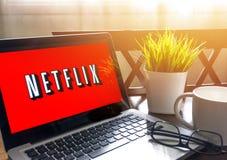Ordenador portátil que exhibe la palabra de Netflix en la tabla de madera imagen de archivo