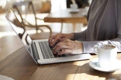 Ordenador portátil que mecanografía en el café horizontal Fotografía de archivo libre de regalías