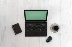Ordenador portátil, ratón del ordenador, taza de café y cuaderno en una tabla de madera Imagenes de archivo