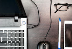 Ordenador portátil, ratón del ordenador, teléfono celular, vidrios y pluma en la tabla Fotografía de archivo