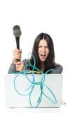 Ordenador portátil sensacional de la mujer enojada usando el martillo fotografía de archivo