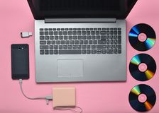 Ordenador portátil, smartphone, banco del poder, unidades de CD, memoria USB en un fondo rosado Medios digitales modernos y antic Fotos de archivo