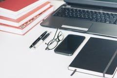 Ordenador port?til, smartphone, pila de libros, plumas, vidrios, cuaderno en la tabla de madera, fondo del concepto de la oficina fotografía de archivo