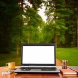 Ordenador portátil sobre la tabla de madera al aire libre y el fondo borroso de árboles en el bosque Fotografía de archivo