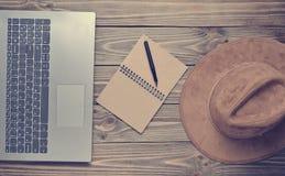 Ordenador portátil, sombrero de fieltro, cuaderno y pluma en una tabla de madera periodismo foto de archivo libre de regalías