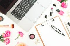Ordenador portátil, tablero, flores de las rosas, cosméticos y accesorios en el fondo blanco Endecha plana Visión superior Concep Fotos de archivo libres de regalías
