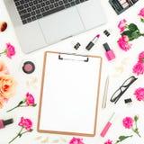 Ordenador portátil, tablero, flores de las rosas, cosméticos y accesorios en el fondo blanco Endecha plana Visión superior Compos Foto de archivo libre de regalías