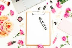 Ordenador portátil, tablero, flores de las rosas, cosméticos y accesorios en el fondo blanco Endecha plana Visión superior Oficin Fotos de archivo libres de regalías