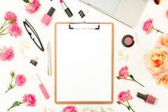 Ordenador portátil, tablero, flores de las rosas, cosméticos y accesorios en el fondo blanco Endecha plana Visión superior Oficin Imagen de archivo libre de regalías